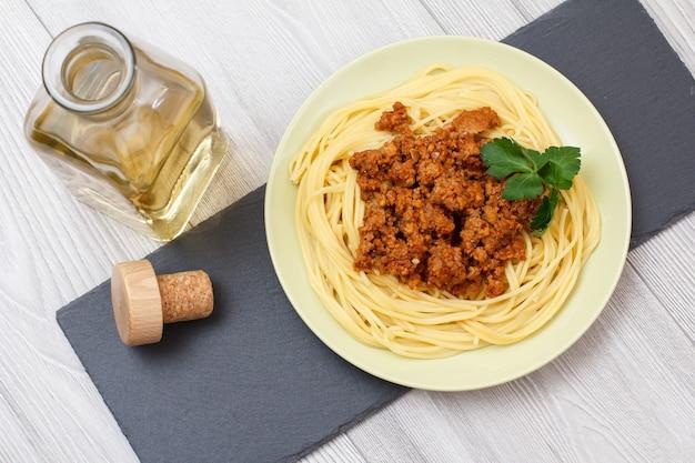 Talerz porcelanowy ze spaghetti i sosem bolońskim, butelka białego wina na czarnej kamiennej desce. widok z góry.