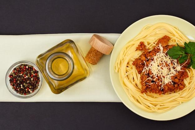 Talerz porcelanowy ze spaghetti i sosem bolońskim, szklana miska z jagodami ziela angielskiego i butelka białego wina na serwetce. widok z góry.