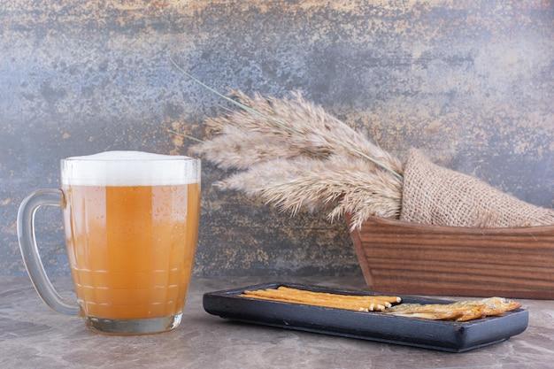Talerz przekąsek i spienione piwo na marmurowym stole. zdjęcie wysokiej jakości