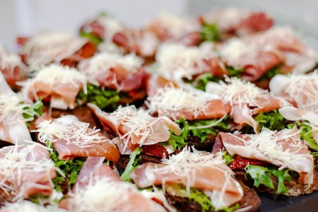 Talerz przekąsek na imprezie: kanapki z szynką prosciutto, suszonymi pomidorami, świeżą sałatą i tartym serem.