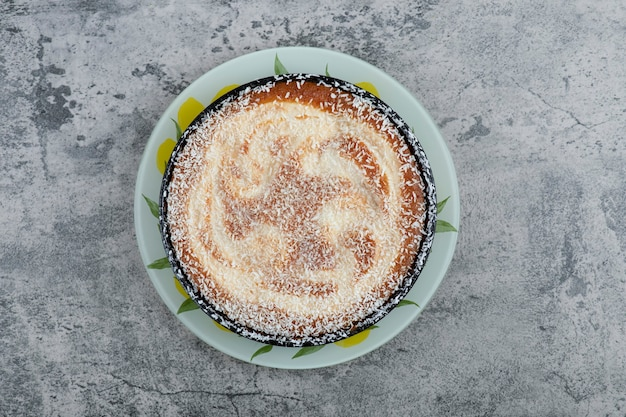 Talerz pysznego ciasta pudrowanego cukrem na drewnianym stole.