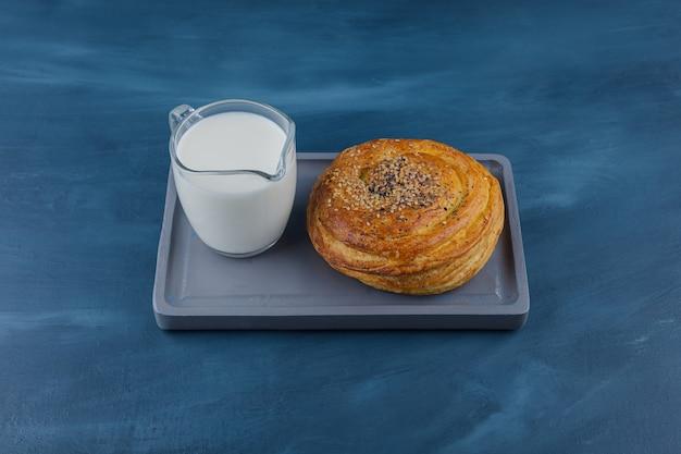 Talerz pysznego ciasta z czarnymi pestkami i szklanką mleka na niebieskiej powierzchni.