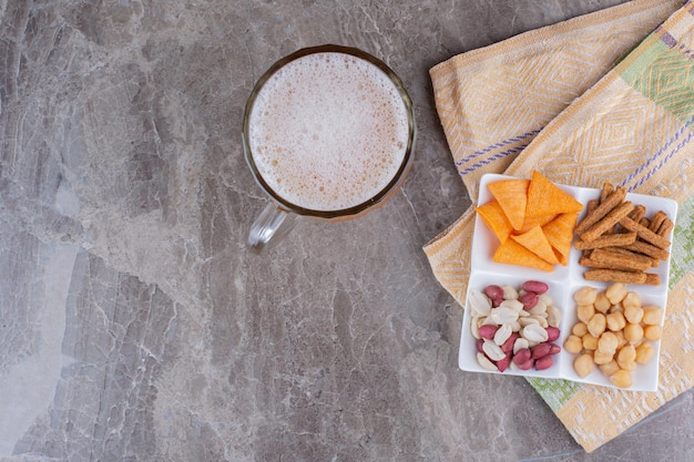 Talerz różnych przekąsek i piwa na marmurowej powierzchni. zdjęcie wysokiej jakości