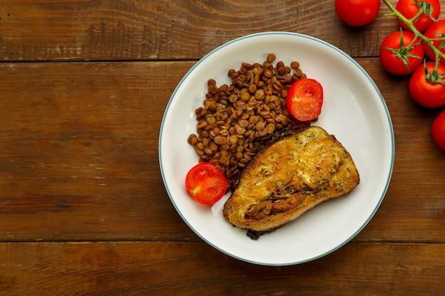 Talerz ryby z soczewicą i pomidorami na drewnianym stole w pobliżu pomidorów.
