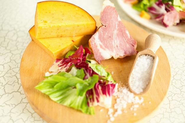 Talerz sałat z zielonych liści, szynki i sera. talerz sałat z zielonymi liśćmi, szynką i serem. świeża sałata, ser, szynka i sól morska na desce do krojenia. śniadanie międzykontynentalne w hotelu.