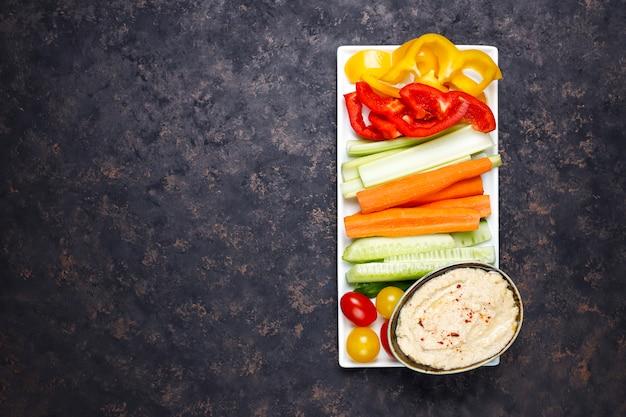 Talerz sałat ze świeżych organicznych warzyw z hummusem na ciemnobrązowej lub betonowej powierzchni