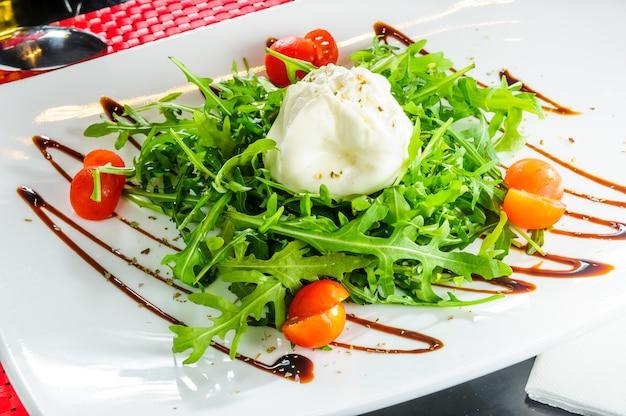 Talerz sałatkowy z mozzarellą, rukolą i pomidorami.