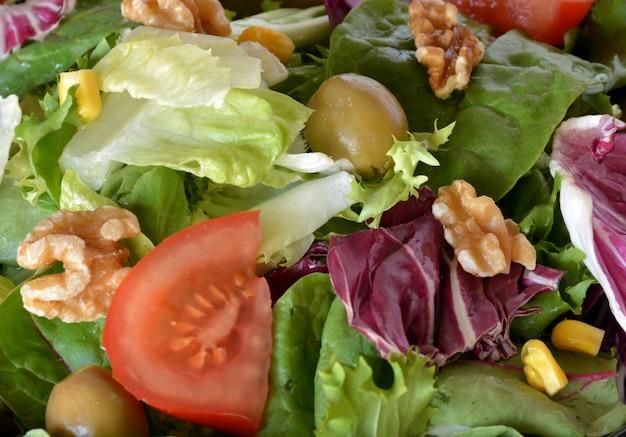 Talerz sałaty z sałatą, pomidorem, oliwkami i oliwą. na czarnym ściereczce