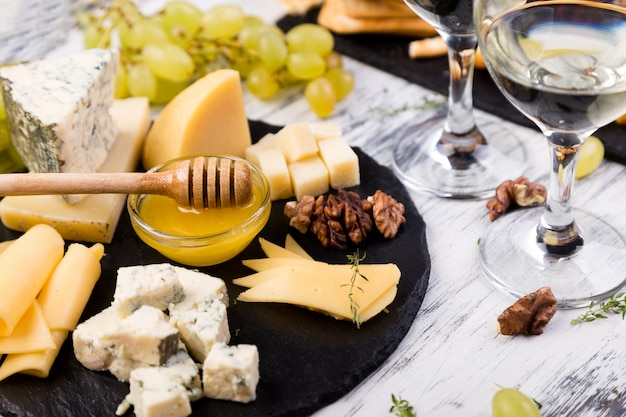Talerz serów asortyment sera z orzechami włoskimi, chleb i miód na kamiennej płycie łupkowej.