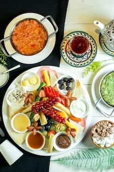 Talerz serów podany z sosem winogronowym i świeżymi owocami