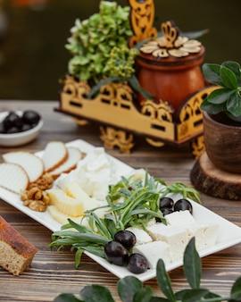 Talerz serów przyozdobiony estragonem i oliwką