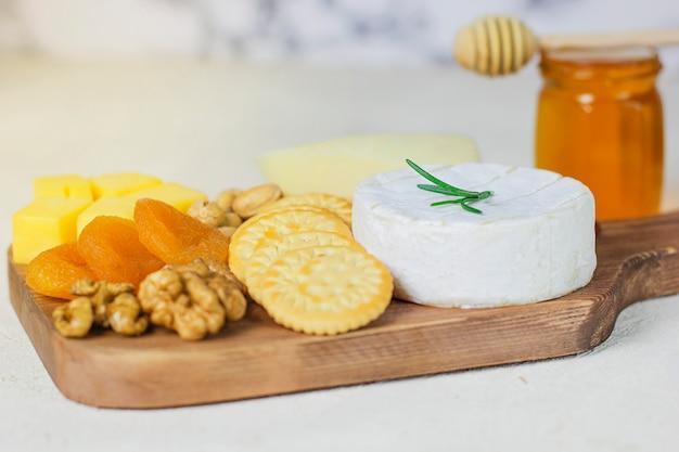 Talerz serów, ser camembert, rozmaryn, krakersy, sucha morela i orzechy włoskie