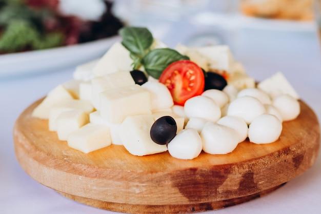 Talerz serów z kiściami winogron, miodu i orzechów. gouda, parmezan, mozzarella, gorgonzola na drewnianej desce.