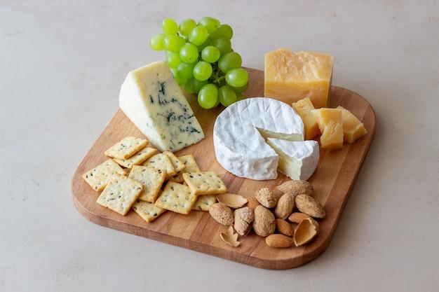 Talerz serów z krakersami, migdałami i winogronami. przystawka do wina. przekąska do wina.