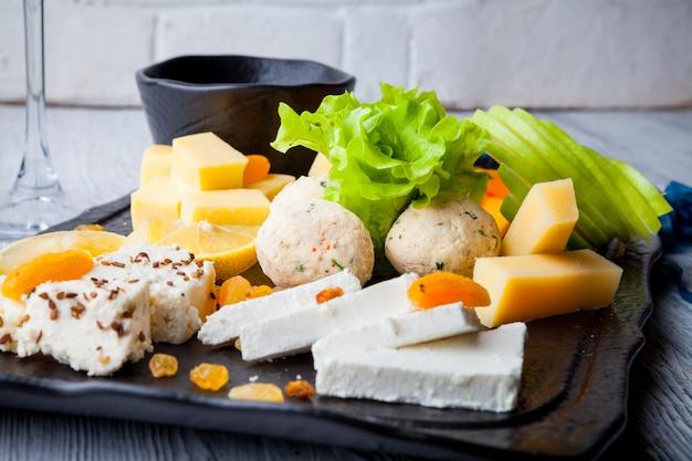 Talerz serów z liśćmi sałatki, rodzynkami i miodem w desce żywności