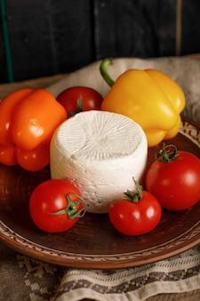 Talerz serów z pomidorami i papryką na rustykalnym ręczniku