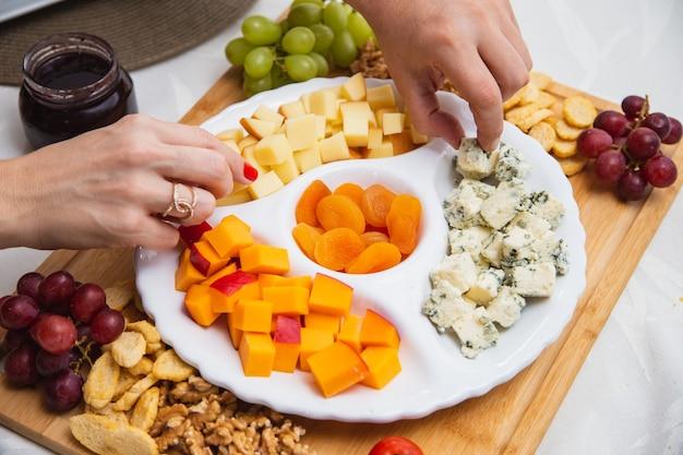Talerz serów z różnymi przystawkami na stole. na stole dania z truskawek, moreli, winogron i serów zbożowych