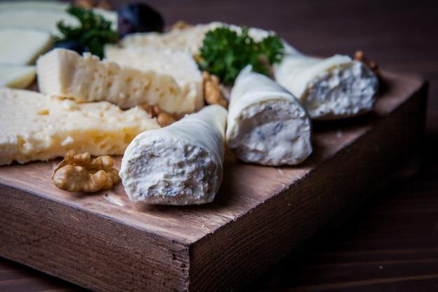 Talerz serów z widokiem z boku, orzech i pietruszka w desce do krojenia