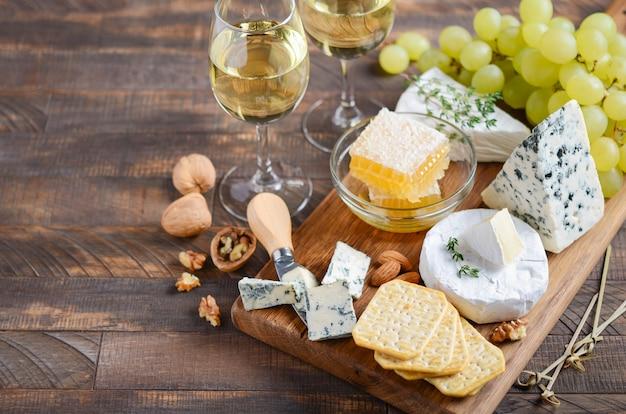 Talerz serów z winogronami, krakersami, miodem i orzechami na drewnianym stole.