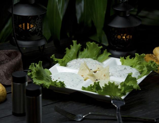 Talerz serów zmieszany z warzywami i podawany z lawaszem