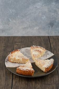 Talerz smaczne ciasto z posypką kokosową na drewnianym stole.