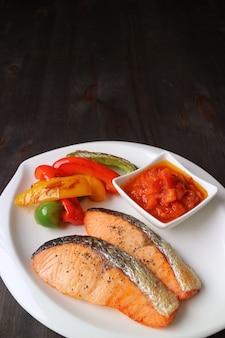 Talerz smażonych na patelni steków z łososia z grillowanymi kolorowymi warzywami podany na ciemnobrązowym drewnianym stole