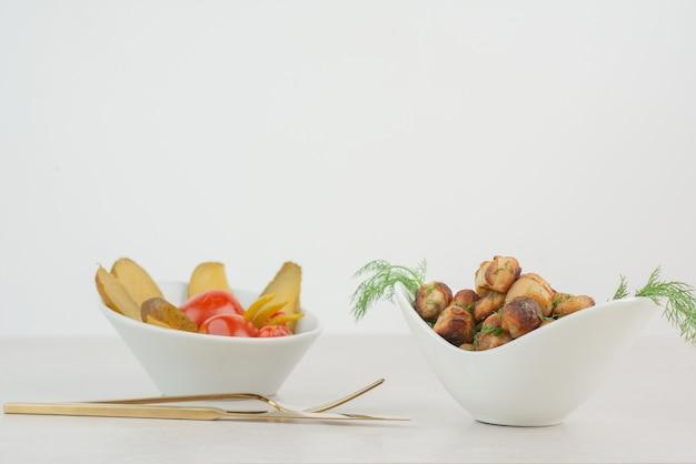 Talerz smażonych ziemniaków i solonych ogórków i pomidorów.