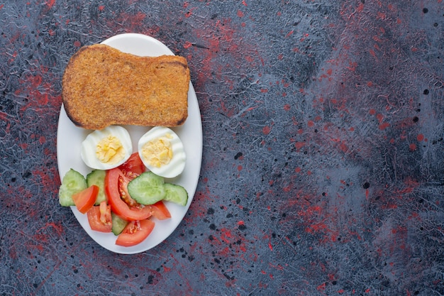 Talerz śniadaniowy z jajkami, ogórkiem i kromkami chleba.