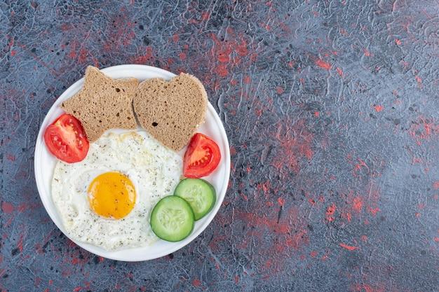Talerz śniadaniowy z jajkiem, ogórkiem, pomidorem i kromkami chleba.