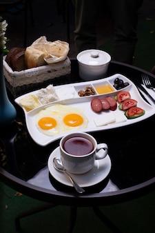 Talerz śniadaniowy z różnorodnymi potrawami, filiżanką herbaty i chleba.
