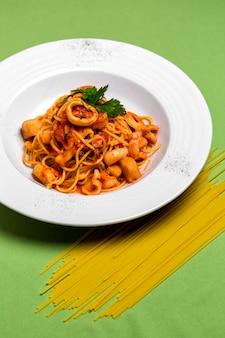 Talerz spaghetti z owocami morza w sosie pomidorowym przyozdobionym natką pietruszki