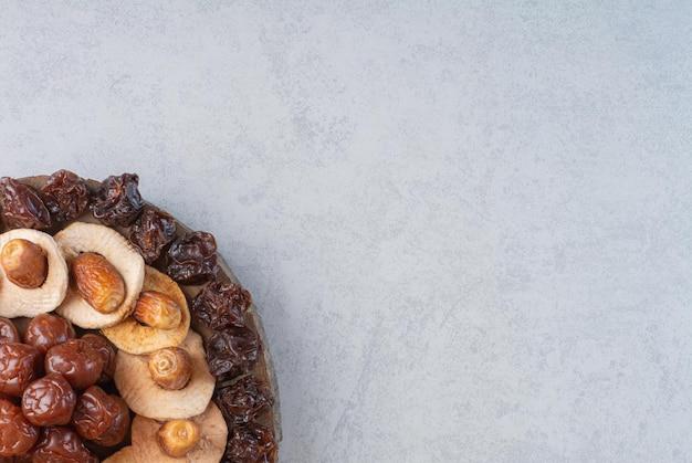 Talerz suszonych owoców na białym tle na betonowym tle.