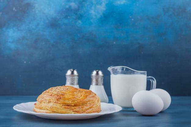 Talerz świeżego okrągłego ciasta z jajkami i mlekiem na niebieskiej powierzchni.