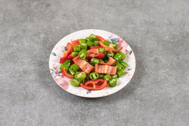 Talerz świeżej sałatki z chili i papryką na powierzchni marmuru.