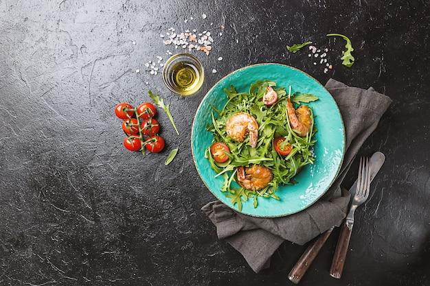 Talerz świeżej sałatki z rukolą lub rukolą, krewetkami i pomidorem, widok z góry.