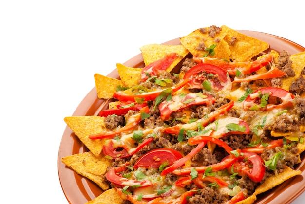 Talerz świeżo przygotowanych pikantnych nachos z wieprzowiną, pomidorem i czerwoną papryką na białym tle