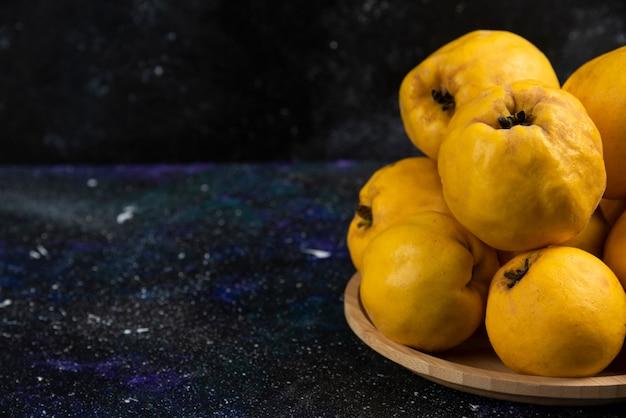 Talerz świeżych owoców pigwy umieszczony na ciemnym stole.
