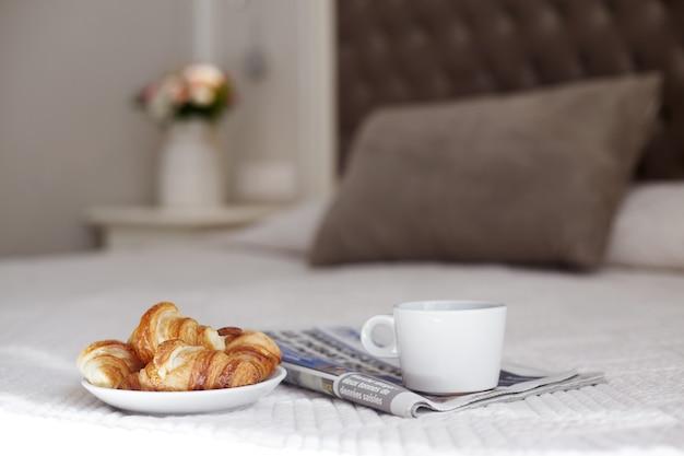 Talerz świeżych rogalików, filiżanka kawy i poranna gazeta na łóżku w pokoju