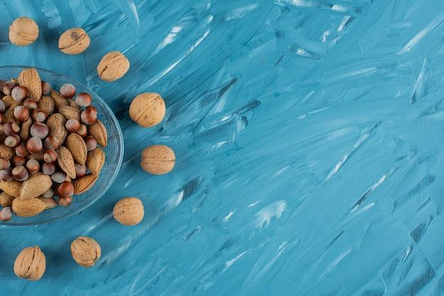 Talerz szklany pełen różnego rodzaju zdrowych, świeżych orzechów na niebieskim tle.