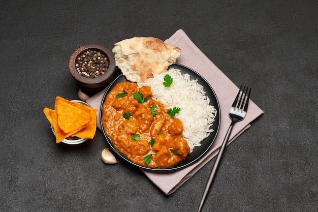 Talerz tradycyjnego curry z kurczaka i ryżu na ciemnym stole