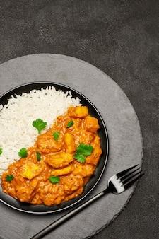 Talerz tradycyjnego curry z kurczaka i ryżu na pokładzie kamienia serwujących
