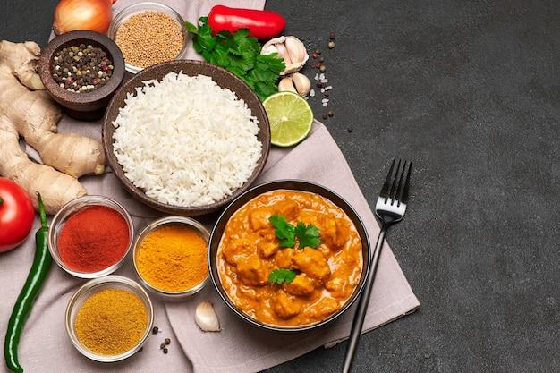 Talerz tradycyjnego kurczaka curry z ryżem i przyprawami na ciemnym stole