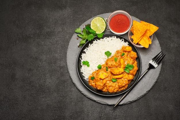 Talerz tradycyjnych nachos curry z kurczaka i ryżu na pokładzie kamienia służących