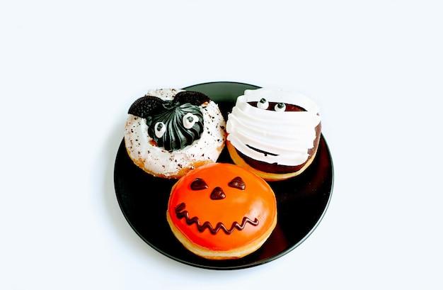 Talerz trzech różnych rodzajów pączków halloween na czarnej płycie na białym tle