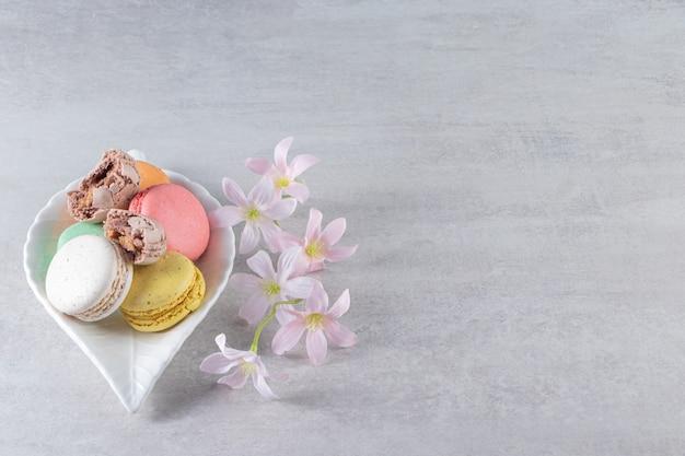 Talerz w kształcie liścia kolorowych słodkich makaroników z kwiatami na kamiennym stole.