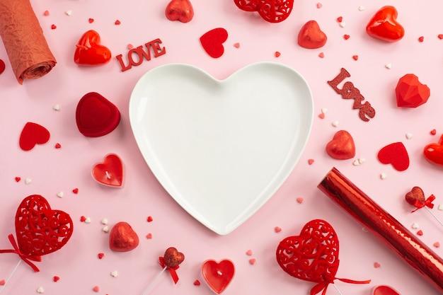 Talerz w kształcie serca z czerwonymi serduszkami, prezentami i świecami.
