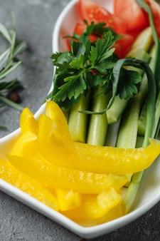 Talerz warzywny z papryką, ogórkami i pomidorami.