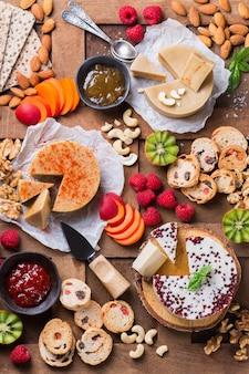 Talerz wędlin podawany z ekologicznym bezmlecznym sfermentowanym serem surowym z orzechów nerkowca z przekąskami, owocami. wegańska, wegetariańska, roślinna żywność, odżywianie i dieta, koncepcja zdrowego odżywiania.