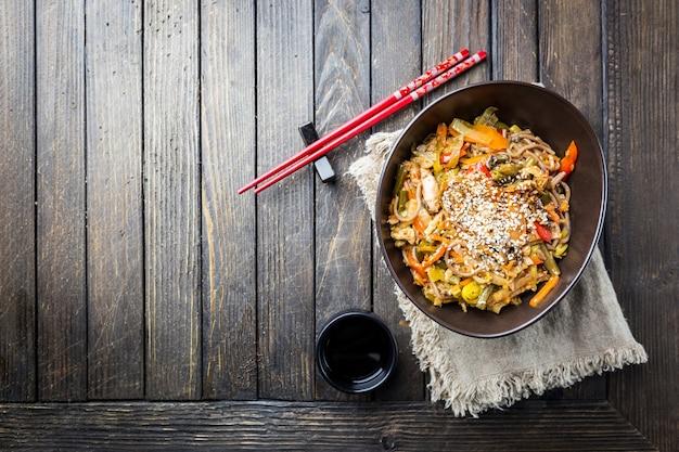 Talerz woka lub makaron smażony z mięsem i warzywami na drewnianym stole