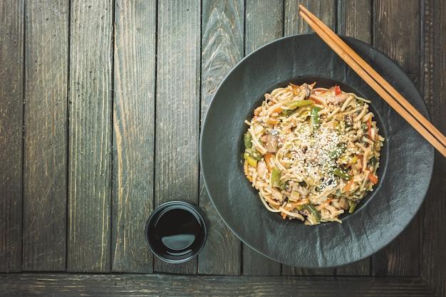 Talerz woka lub smażony makaron z mięsem i warzywami na drewnianym stole
